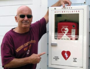 Joe standing next to an AED, the device that saved his life.