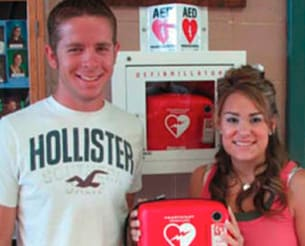 Lindsay holds an AED like the one that saved her life.