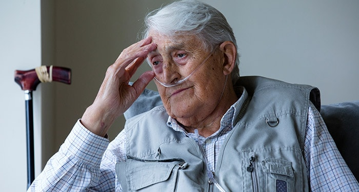 Seated elderly man wearing nasal canula considering his future