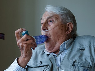 Elderly gentleman using an OptiChamber Diamond spacer with his inhaler whilst wearing a nasal canula