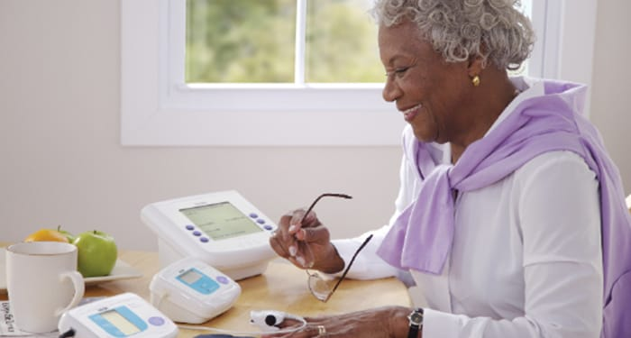 Lady sitting at desk using a pulse oximeter