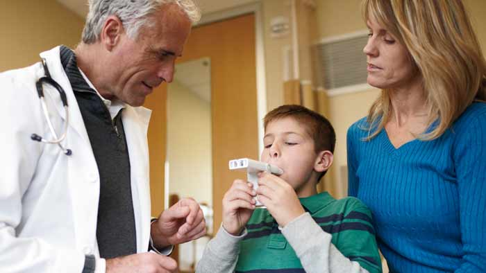 healthcare professional helping kid with asthma product